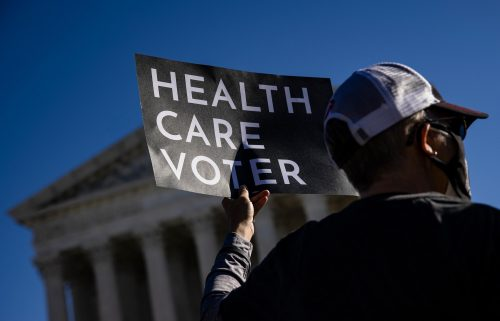 A supporter of the Affordable Care Act (ACA) stands in front of the Supreme Court of the United States in 2020.
