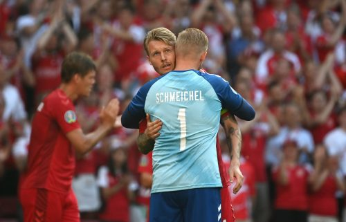 Simon Kjaer and Kasper Schmeichel of Denmark interact as the ball is kicked out of play in the tenth minute followed by a minute of applause in support of Denmark International Christian Eriksen.