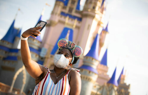 A guest stops to take a selfie at Magic Kingdom Park at Walt Disney World Resort on July 11