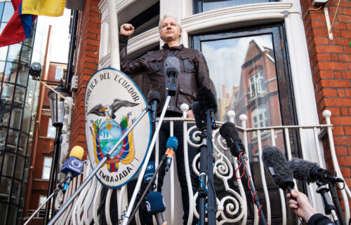 Julian Assange raises his fist as he steps out to speak to the media from the balcony of the Embassy Of Ecuador on May 19