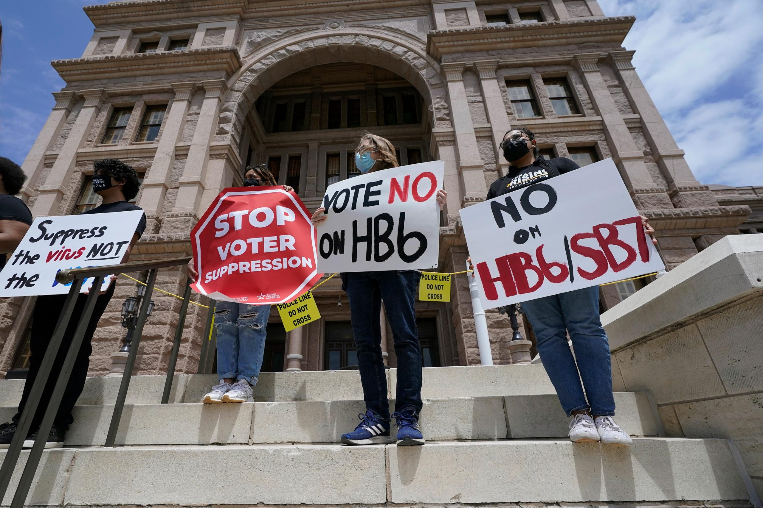 <i>Eric Gay/AP</i><br/>People opposed to Texas voter bills HB6 and SB7 hold signs during a news conference hosted by Texas Rising Action on the steps of the State Capitol in Austin