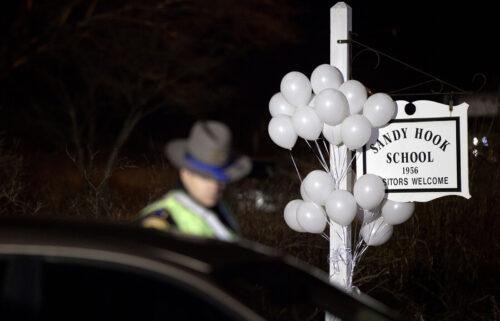 White balloons decorate the sign for the Sandy Hook Elementary School as a Connecticut State Trooper stands guard at the school's entrance in 2012 in Newtown