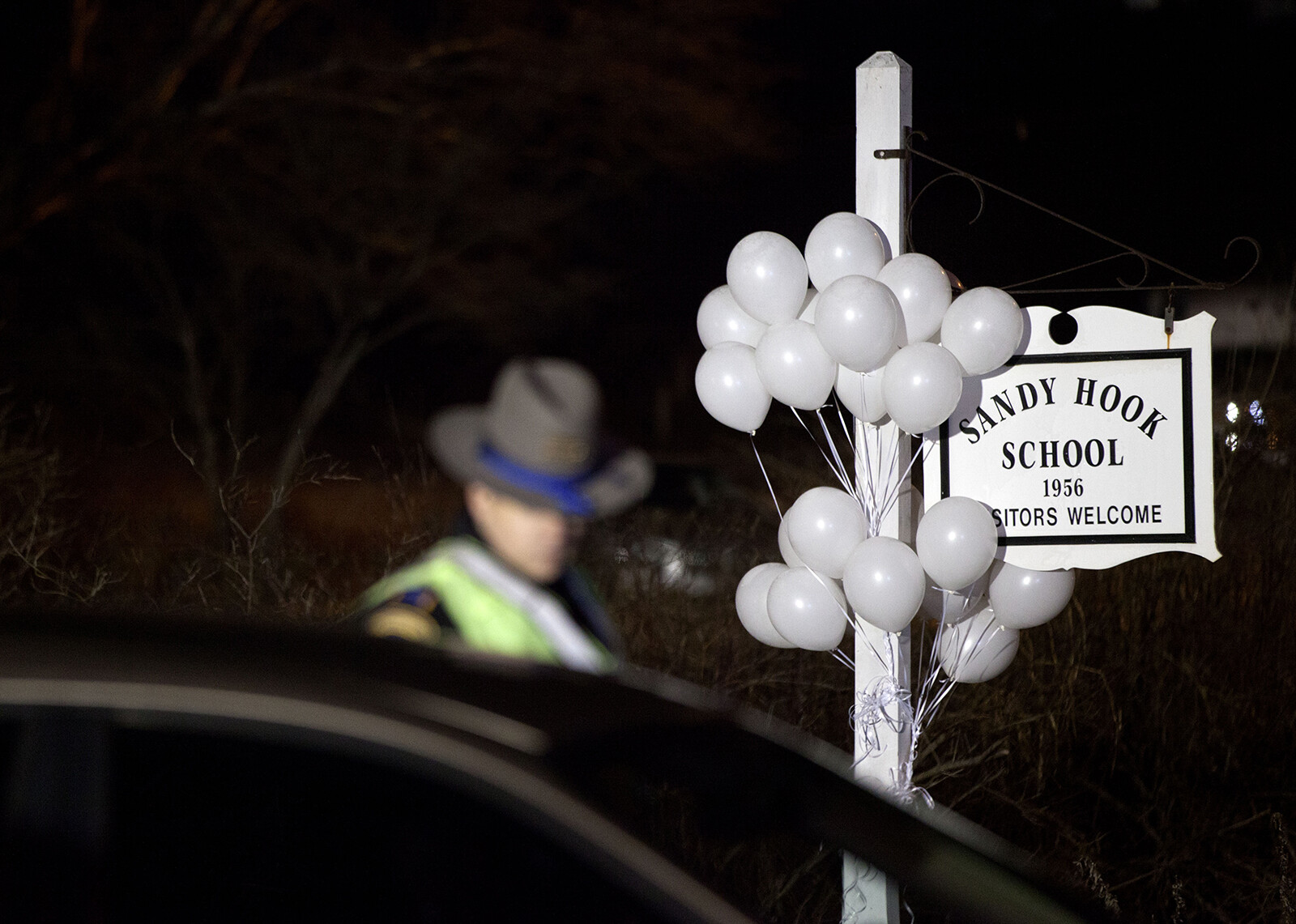 <i>David Goldman/AP</i><br/>White balloons decorate the sign for the Sandy Hook Elementary School as a Connecticut State Trooper stands guard at the school's entrance in 2012 in Newtown
