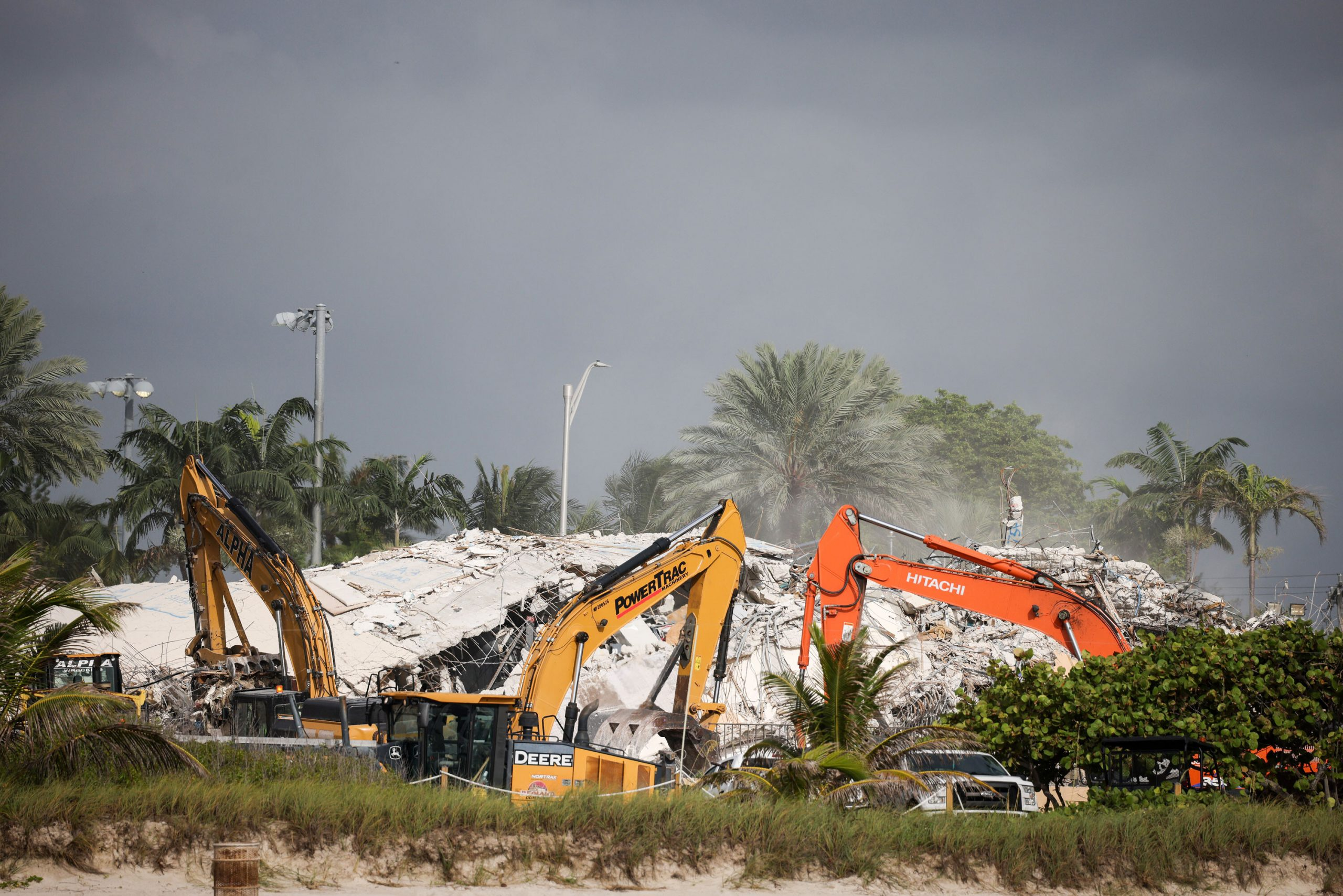 <i>Anna Moneymaker/Getty Images</i><br/>Rescue workers use excavators to dig through the rubble of the collapsed 12-story Champlain Towers South condo building on July 9 in Surfside