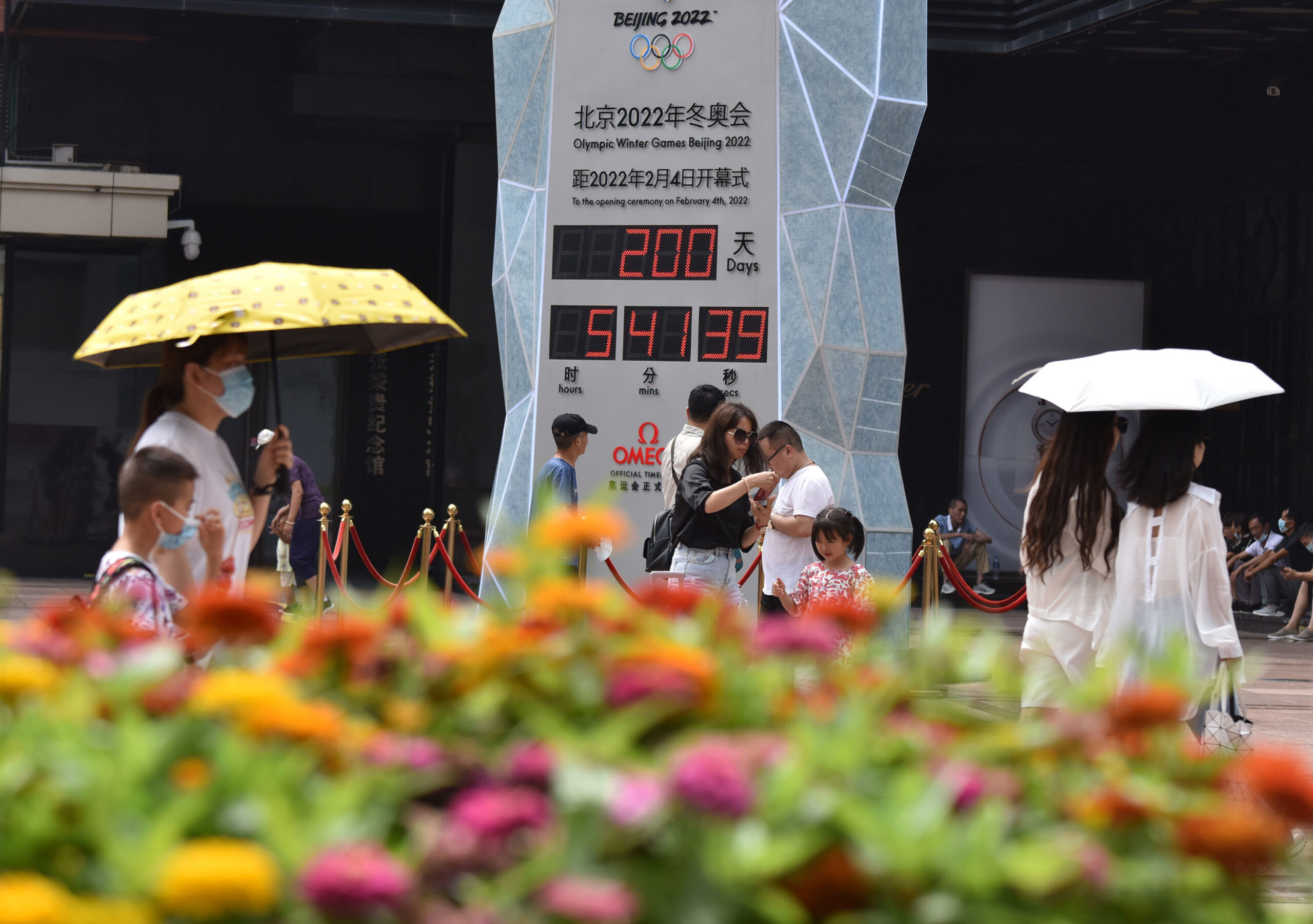 <i>Sheldon Cooper/SOPA Images/LightRocket/Getty Images</i><br/>People wearing face masks walk past the countdown clock showing 200 days to the 2022 Olympic Winter Games.