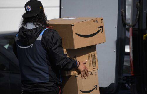 An Amazon.com Inc. delivery driver carries boxes into a van outside of a distribution facility on February 2 in Hawthorne