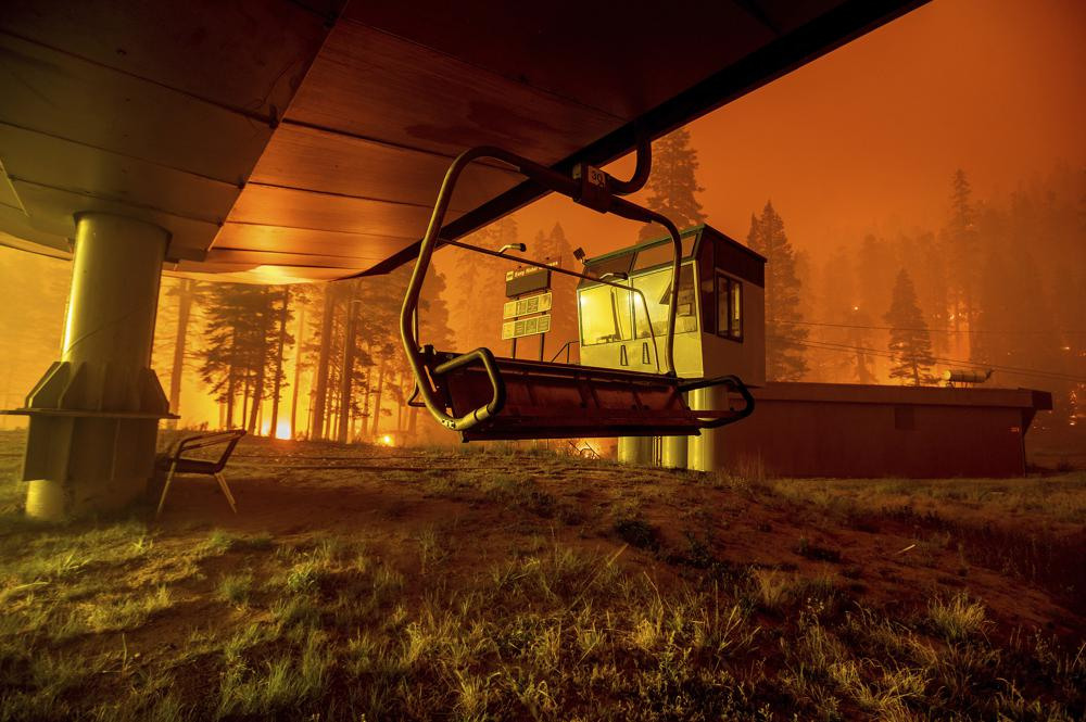 Seen in a long camera exposure, the Caldor Fire burns at Sierra-at-Tahoe ski resort on Monday, Aug. 30, 2021, in Eldorado National Forest, Calif. The main buildings at the ski slope's base survived as the main fire front passed.