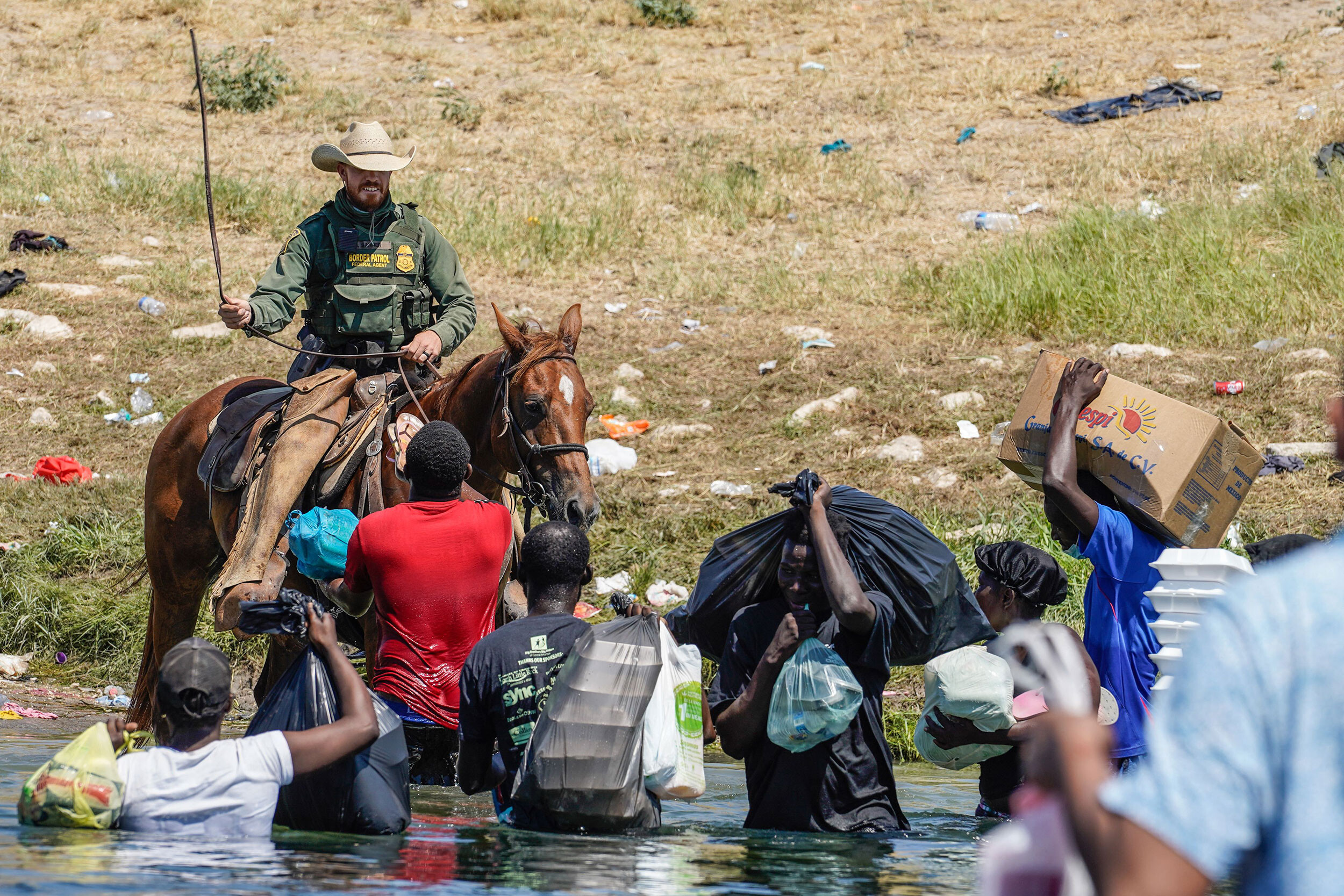 <i>Paul Ratje/AFP/Getty Images</i><br/>A United States Border Patrol agent on horseback uses the reins as he tries to stop Haitian migrants from entering an encampment on the banks of the Rio Grande near the Acuna Del Rio International Bridge in Del Rio