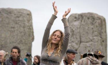 A woman dances as druids