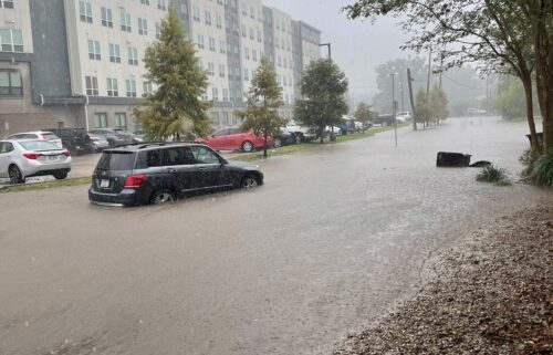 Nearly 5 million people are under flash flood watches as Post-Tropical Cyclone Nicholas hovers over the Gulf region. A car here passes through flooding in Baton Rouge