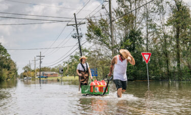 Residents move a cart with gas cans through a flooded neighborhood on Tuesday in Barataria