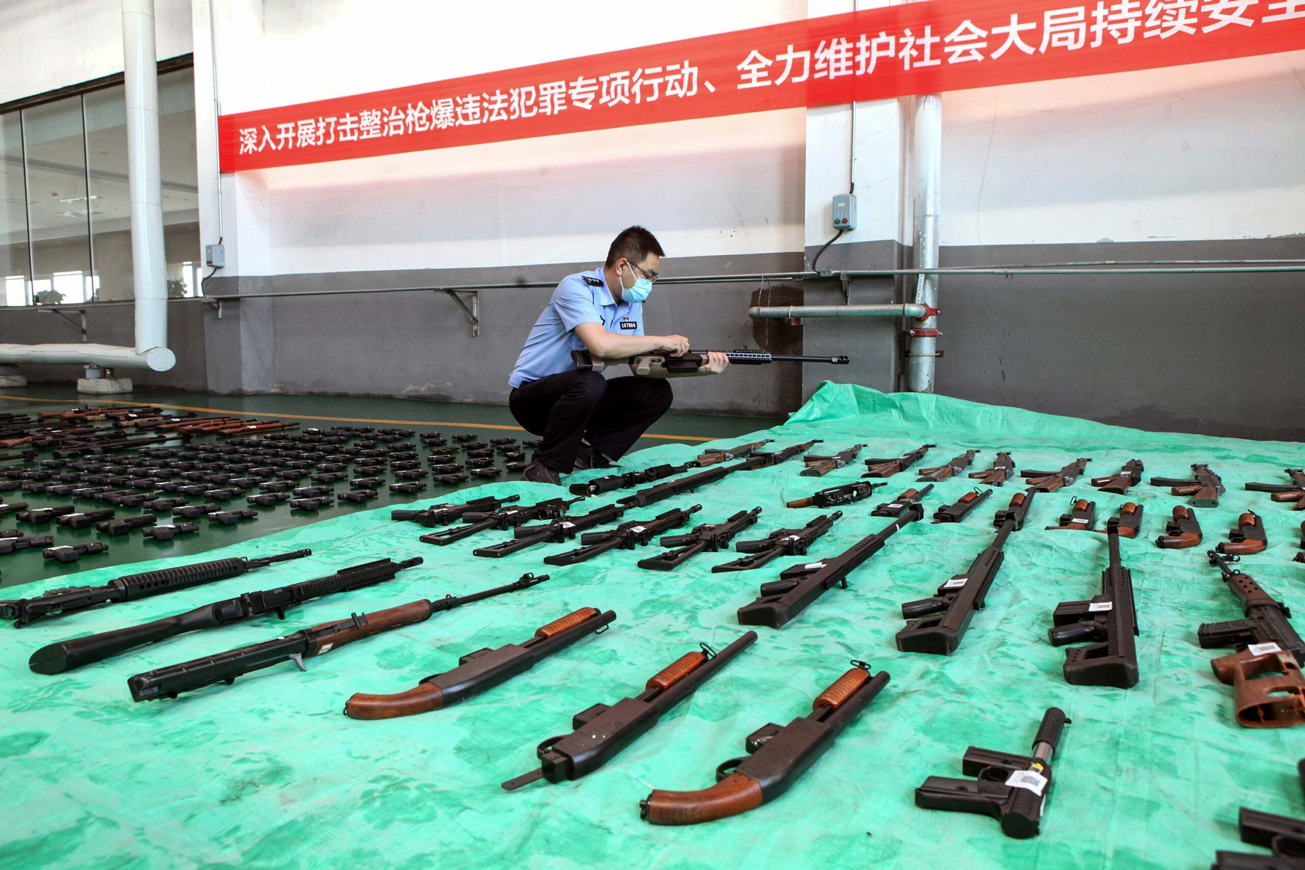 <i>STR/AFP/Getty Images</i><br/>A police officer inspects confiscated illegal guns slated for destruction at an incineration facility in Shenyang
