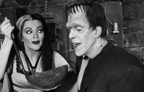"""Lily Munster (Yvonne De Carlo) holds a giant ladle for Herman Munster (Fred Gwynne) in an episode of the original """"The Munsters."""""""