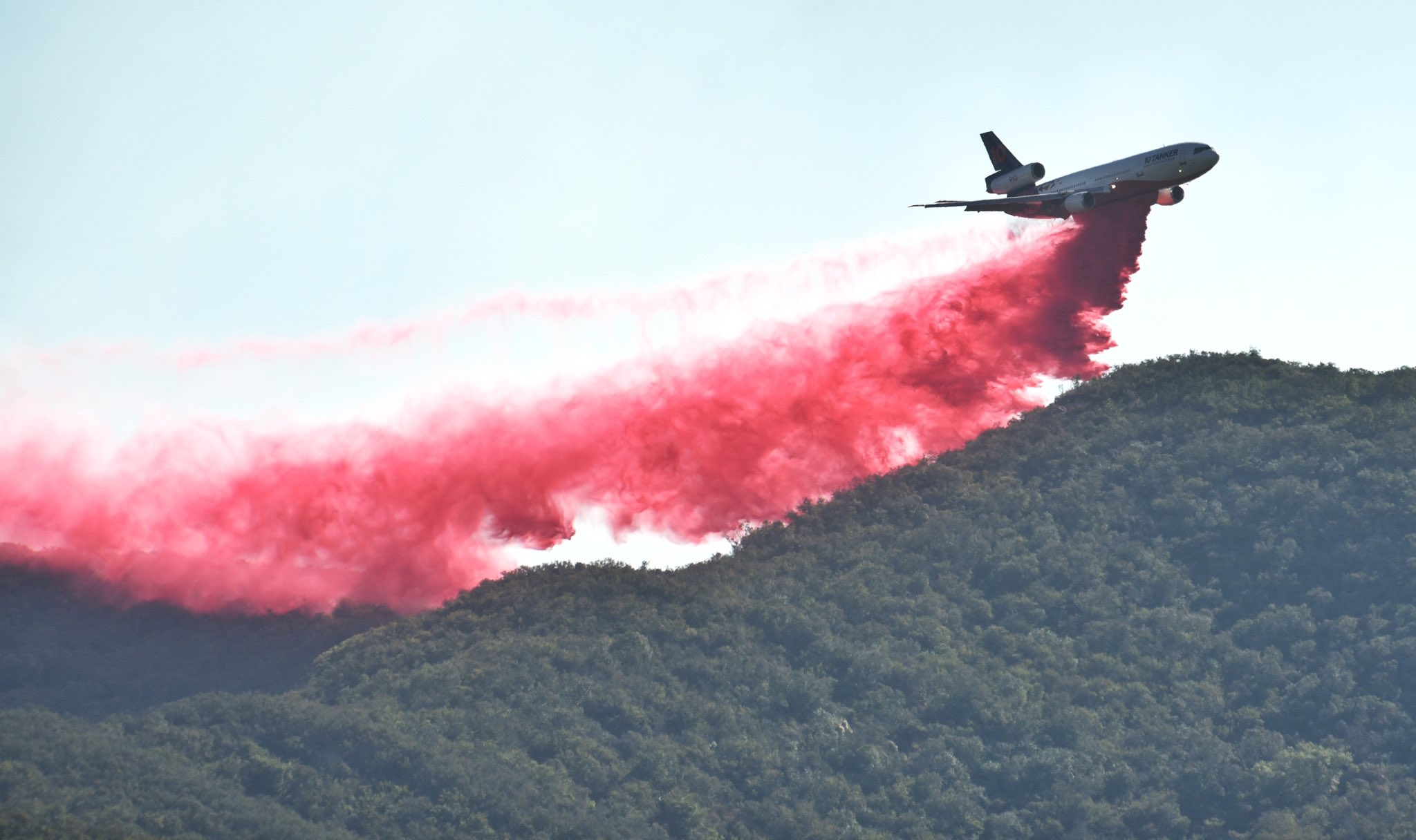 A fixed-wing aircraft makes a retardant drop on the Alisal Fire