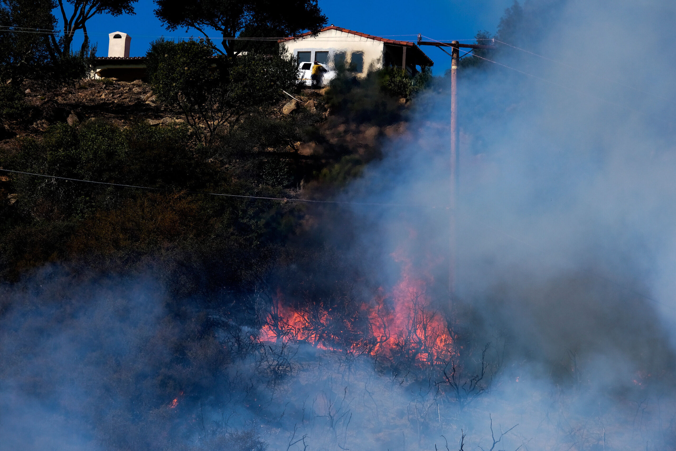 <i>Ringo H.W. Chiu/AP</i><br/>A wildfire raging through Southern California's coastal mountains threatened ranches and rural homes and kept a major highway shut down Wednesday as the fire-scarred state faced a new round of dry winds that raise risk of flames.