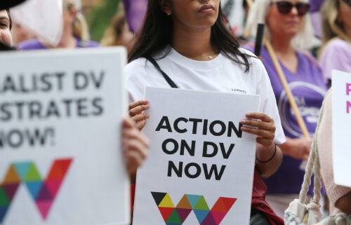 Women hold signs urging action against domestic violence during the 2020 International Women's Day march in Sydney.
